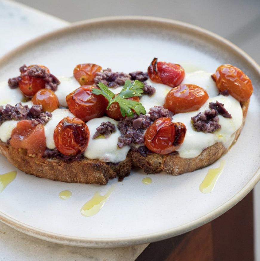Panela Mágica serve toast com mozzarella de búfula tomate cereja e azeitona